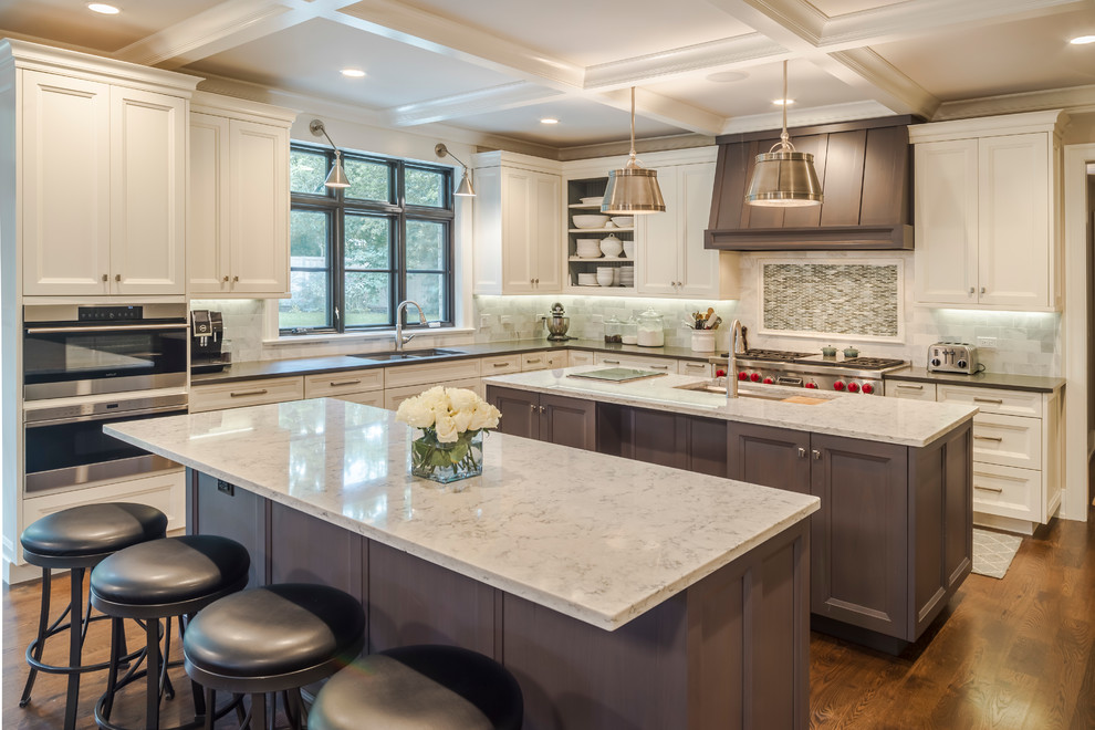 Example of a huge classic l-shaped dark wood floor and brown floor kitchen design in Chicago with an undermount sink, quartz countertops, stainless steel appliances, two islands, recessed-panel cabinets, white cabinets, multicolored backsplash and mosaic tile backsplash