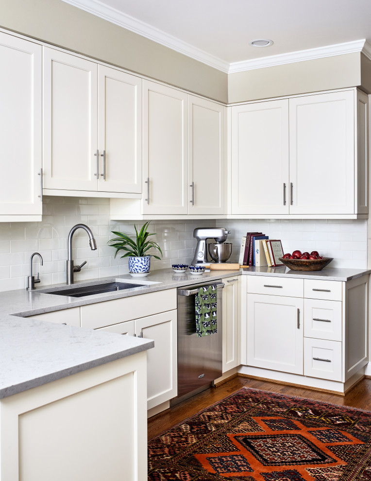Inspiration for a mid-sized transitional u-shaped medium tone wood floor and brown floor enclosed kitchen remodel in DC Metro with an undermount sink, shaker cabinets, white cabinets, quartzite countertops, white backsplash, subway tile backsplash, stainless steel appliances, a peninsula and gray countertops