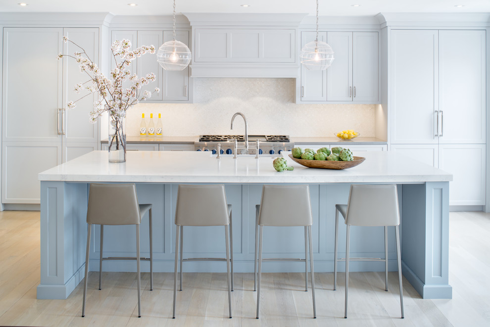 Kitchen - transitional galley light wood floor and beige floor kitchen idea in DC Metro with recessed-panel cabinets, blue cabinets, white backsplash, stainless steel appliances, an island and white countertops
