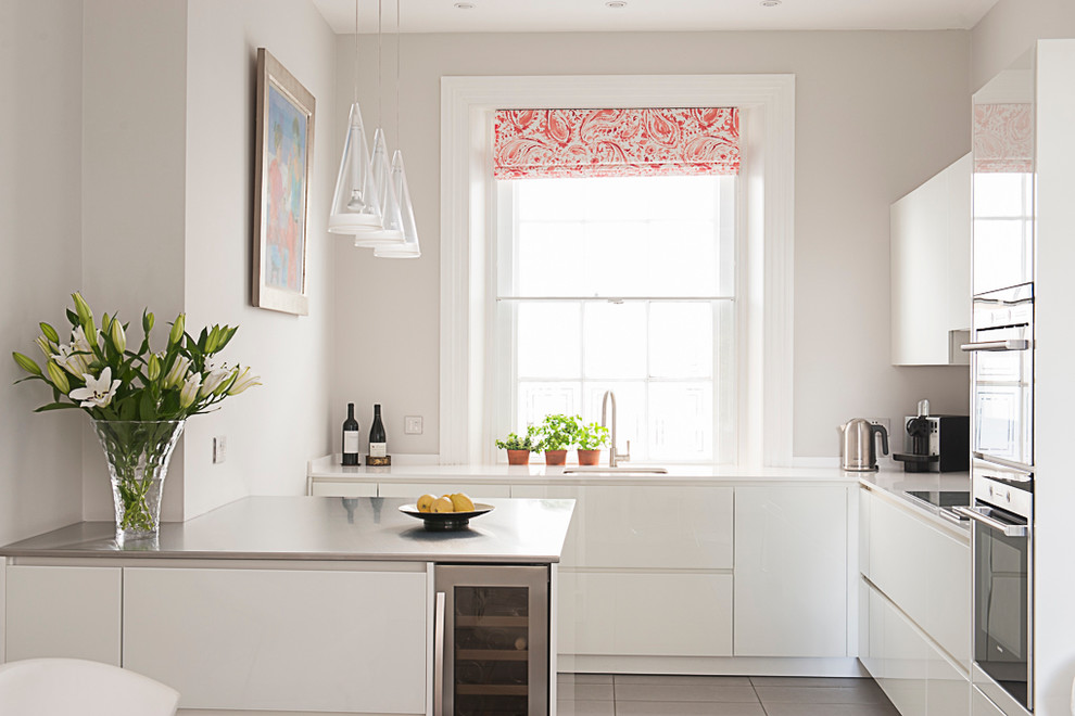 Trendy l-shaped kitchen photo in Kent with an undermount sink, flat-panel cabinets, white cabinets, stainless steel appliances and a peninsula
