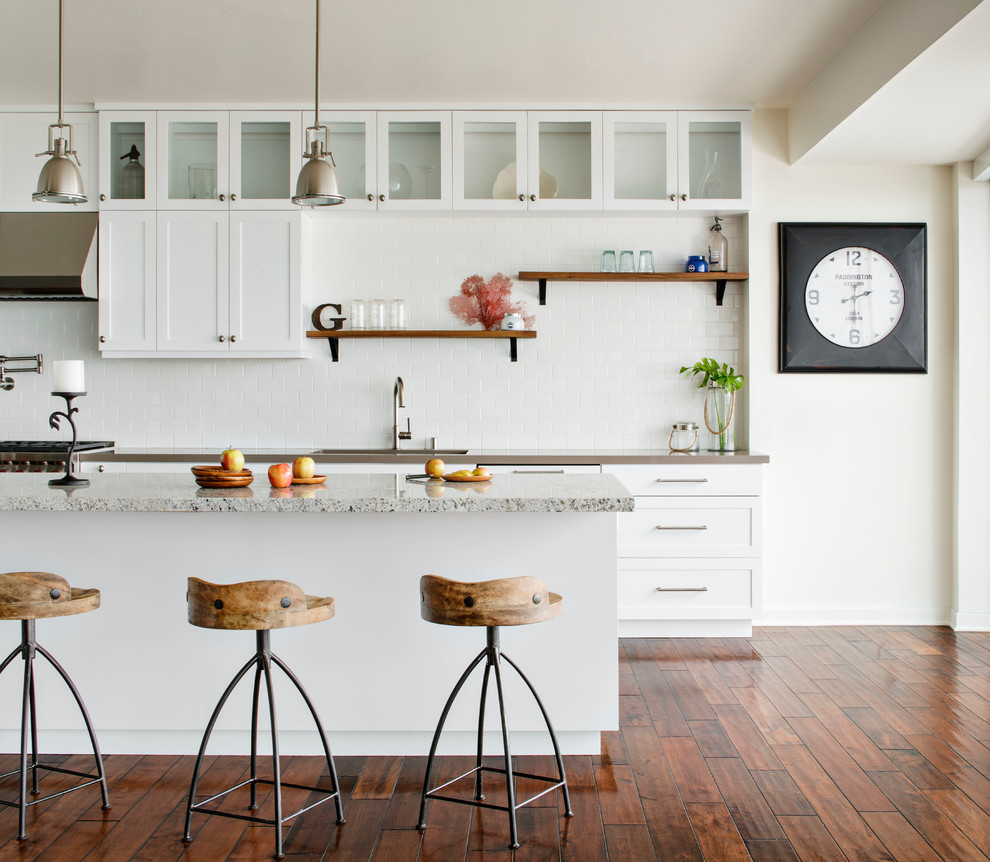Example of a mid-sized coastal galley medium tone wood floor eat-in kitchen design in San Francisco with shaker cabinets, white cabinets, white backsplash, subway tile backsplash and an island