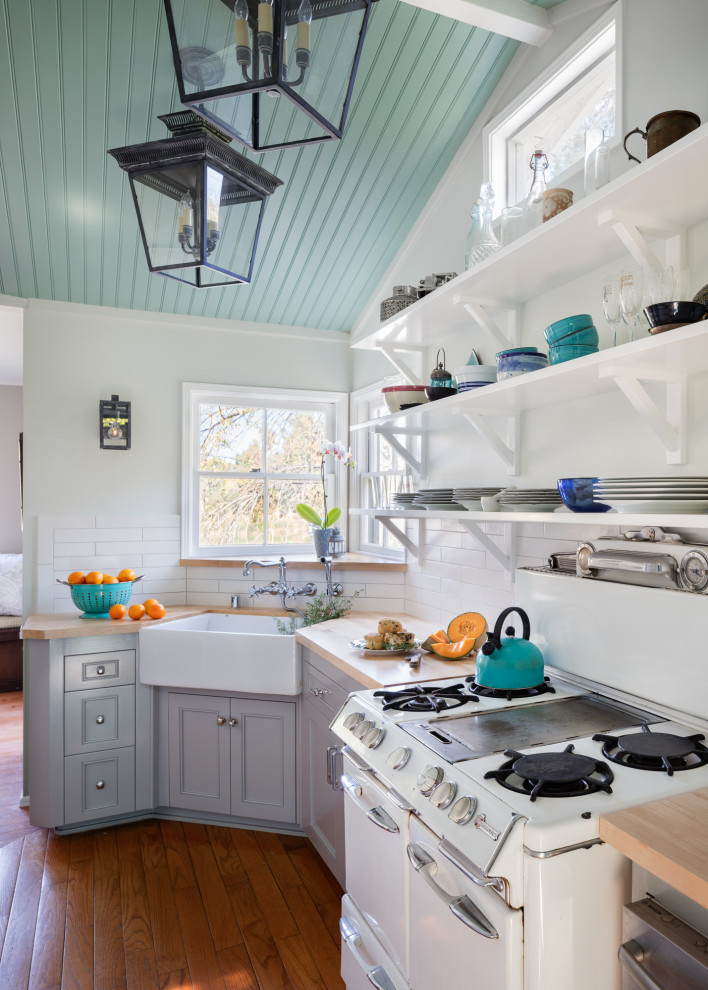 Example of a small beach style galley medium tone wood floor and brown floor enclosed kitchen design in Los Angeles with a farmhouse sink, shaker cabinets, gray cabinets, wood countertops, white backsplash, ceramic backsplash, white appliances, no island and beige countertops