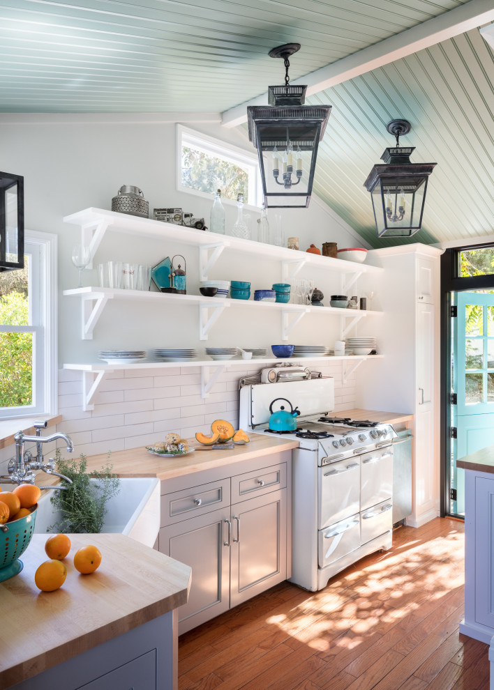 Enclosed kitchen - small coastal l-shaped medium tone wood floor, brown floor and vaulted ceiling enclosed kitchen idea in Los Angeles with a farmhouse sink, gray cabinets, wood countertops, white backsplash, ceramic backsplash, white appliances, no island, beige countertops and recessed-panel cabinets