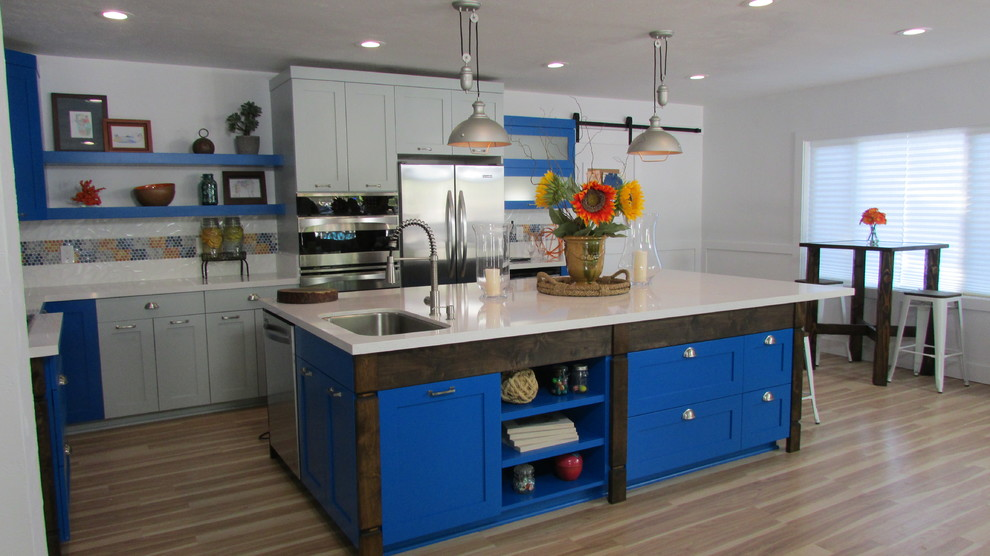 Example of a mid-sized transitional l-shaped light wood floor eat-in kitchen design in Sacramento with an undermount sink, shaker cabinets, gray cabinets, porcelain backsplash, stainless steel appliances and an island