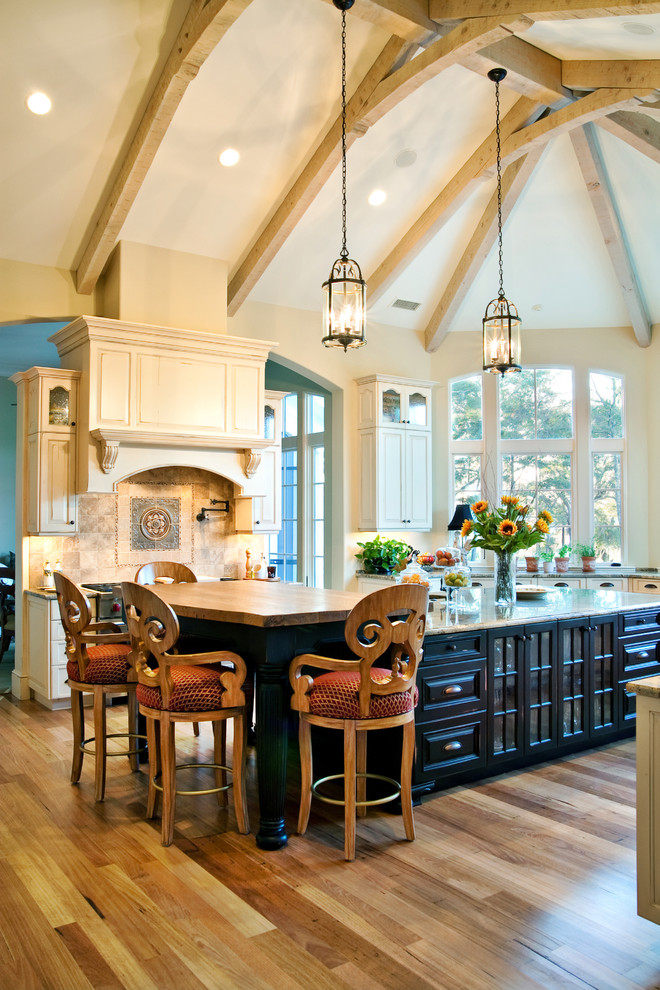 Elegant kitchen photo in Charleston with raised-panel cabinets and wood countertops