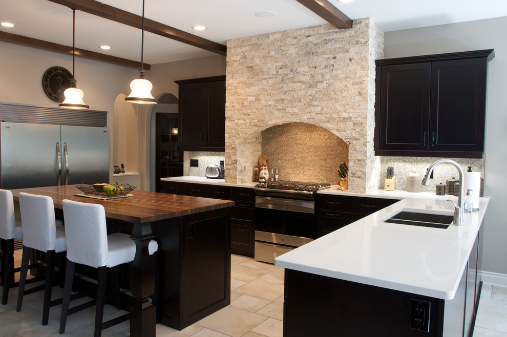 Eat-in kitchen - large transitional u-shaped travertine floor eat-in kitchen idea in Edmonton with a double-bowl sink, shaker cabinets, black cabinets, solid surface countertops, multicolored backsplash, mosaic tile backsplash, stainless steel appliances and an island
