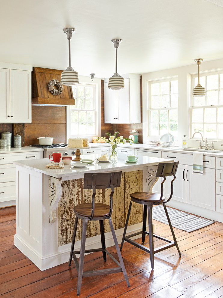 Example of a country l-shaped medium tone wood floor and brown floor kitchen design in Cleveland with an undermount sink, shaker cabinets, white cabinets, quartz countertops, brown backsplash, an island, wood backsplash and white countertops