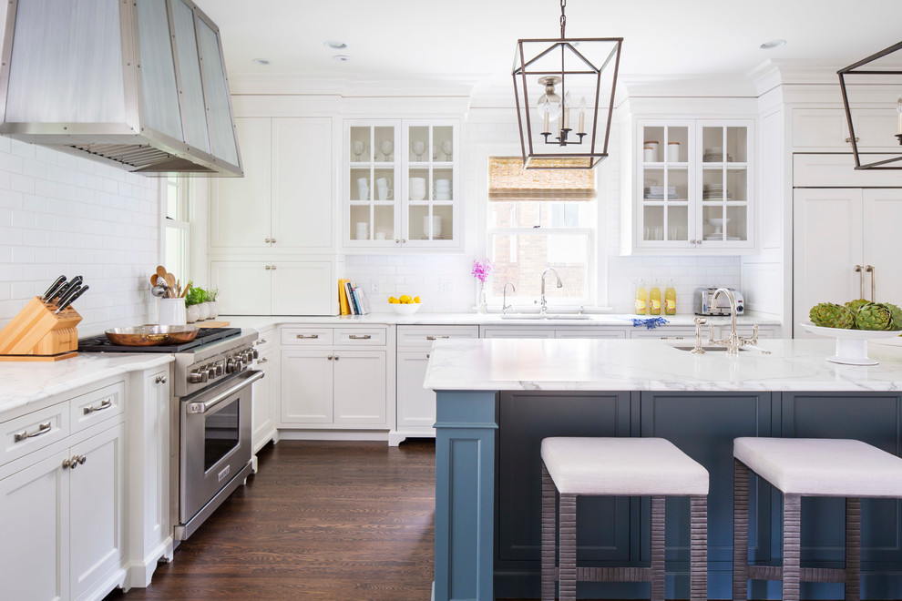 Elegant l-shaped dark wood floor kitchen photo in Minneapolis with an undermount sink, glass-front cabinets, white cabinets, white backsplash, subway tile backsplash, stainless steel appliances, an island and marble countertops