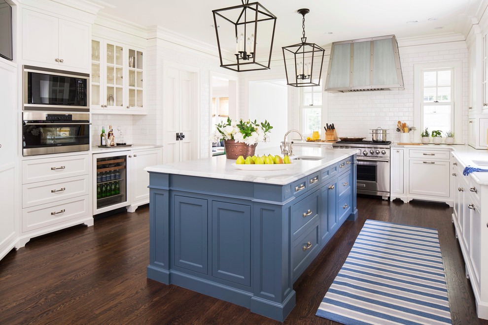 Example of a classic l-shaped dark wood floor kitchen design in Minneapolis with an undermount sink, shaker cabinets, white cabinets, marble countertops, white backsplash, subway tile backsplash, stainless steel appliances and an island