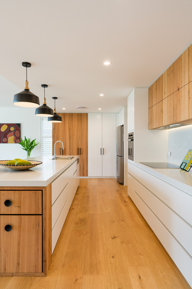 Photo of a large contemporary galley kitchen in Other with a drop-in sink, flat-panel cabinets, white cabinets, white splashback, medium hardwood floors, with island, brown floor and white benchtop.