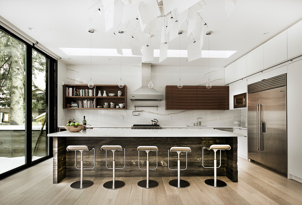 Kitchen - modern l-shaped light wood floor kitchen idea in Toronto with an island, a double-bowl sink, flat-panel cabinets, medium tone wood cabinets, marble countertops, white backsplash and stainless steel appliances