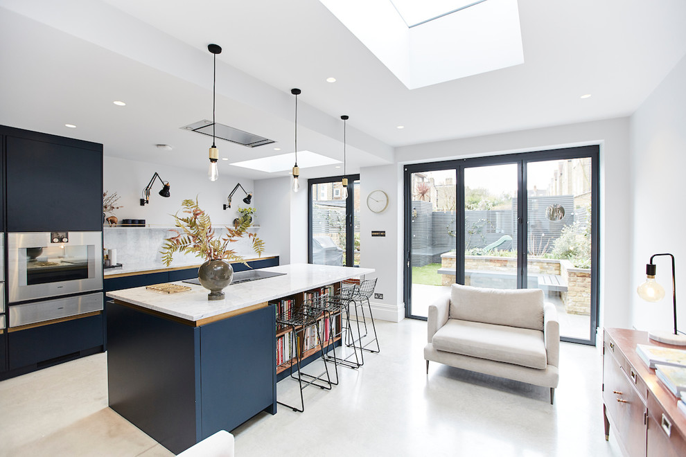 Inspiration for a mid-sized scandinavian concrete floor open concept kitchen remodel in London with flat-panel cabinets, blue cabinets, marble countertops, white backsplash, marble backsplash, stainless steel appliances, an island and white countertops