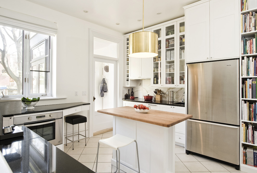 Mid-sized trendy ceramic tile and beige floor enclosed kitchen photo in Montreal with glass-front cabinets, wood countertops, white cabinets, stainless steel appliances, white backsplash, stone slab backsplash and an island