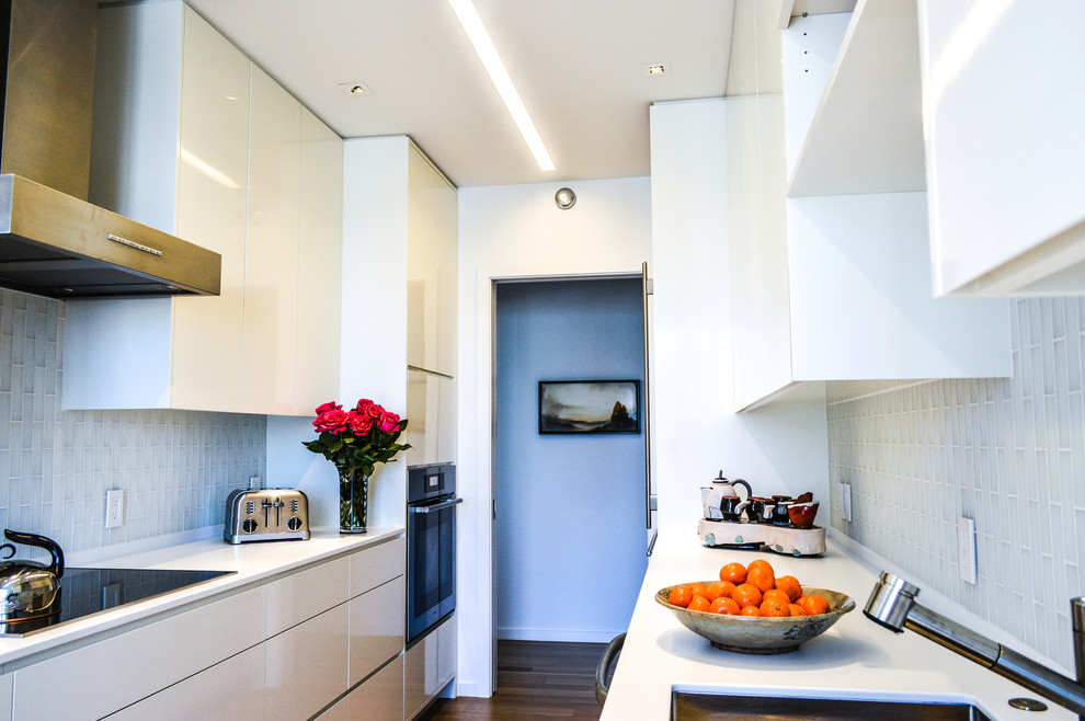 Small minimalist galley light wood floor enclosed kitchen photo in San Francisco with an undermount sink, flat-panel cabinets, yellow cabinets, quartzite countertops, yellow backsplash, glass tile backsplash, stainless steel appliances and white countertops