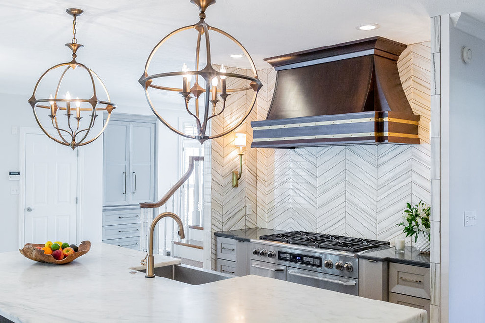 Example of a large minimalist u-shaped porcelain floor and gray floor kitchen design in Other with a farmhouse sink, gray cabinets, marble countertops, gray backsplash, marble backsplash, stainless steel appliances, an island and multicolored countertops