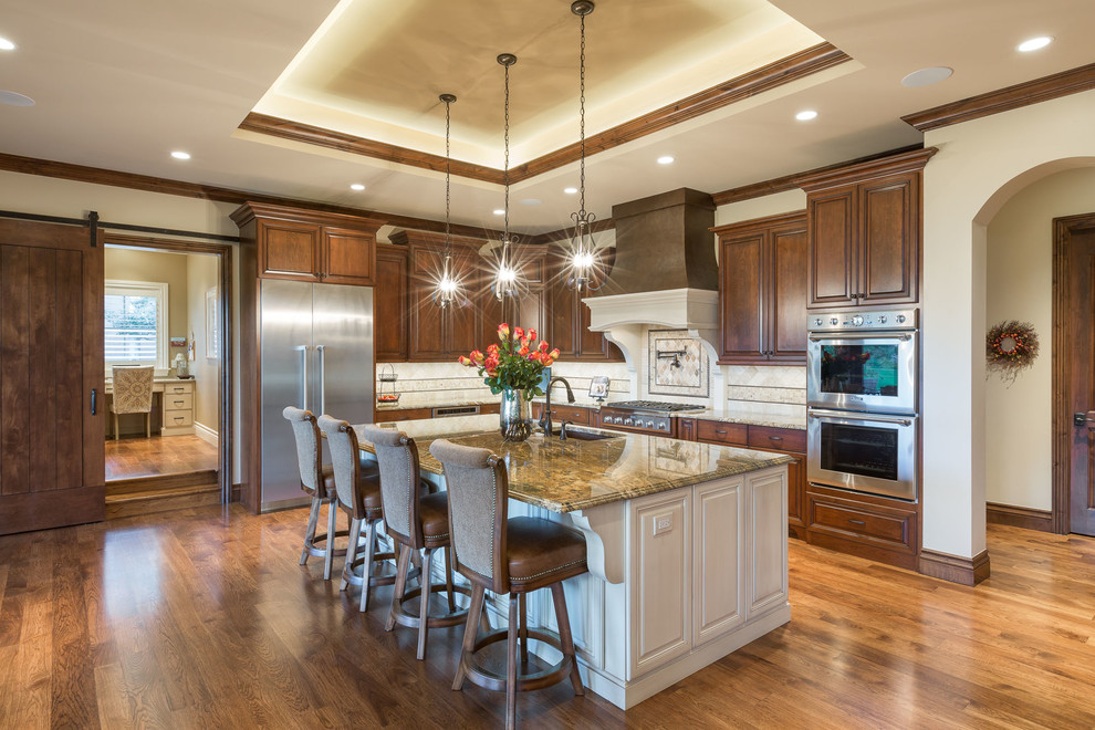 Large mountain style l-shaped medium tone wood floor and brown floor eat-in kitchen photo in Denver with raised-panel cabinets, dark wood cabinets, granite countertops, stainless steel appliances, an island, an undermount sink, multicolored backsplash, ceramic backsplash and multicolored countertops