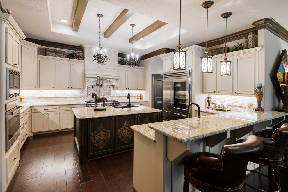 Elegant u-shaped dark wood floor and brown floor kitchen photo in Houston with shaker cabinets, white cabinets, stainless steel appliances, no island and beige countertops