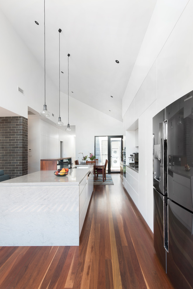This is an example of a contemporary galley open plan kitchen in Newcastle - Maitland with an undermount sink, flat-panel cabinets, white cabinets, stainless steel appliances, dark hardwood floors, an island, brown floor and grey benchtop.