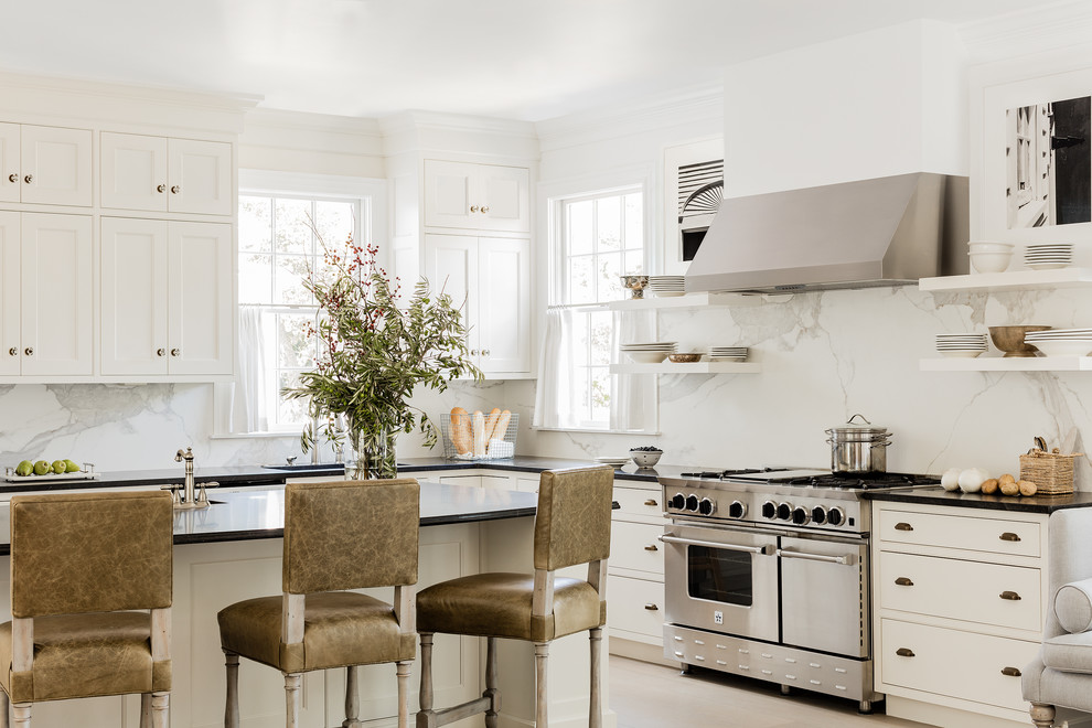 Kitchen - coastal l-shaped light wood floor and beige floor kitchen idea with shaker cabinets, white cabinets, granite countertops, white backsplash, marble backsplash, stainless steel appliances, an island and black countertops
