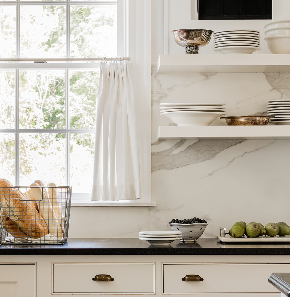 Kitchen - transitional light wood floor and gray floor kitchen idea with shaker cabinets, white cabinets, granite countertops, white backsplash, marble backsplash, stainless steel appliances, an island and black countertops