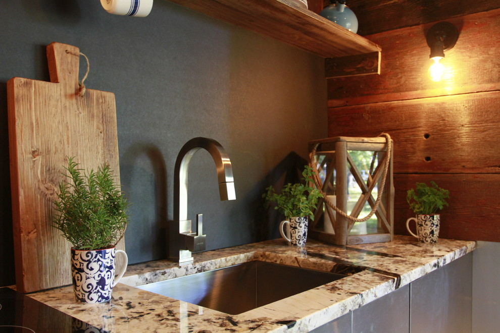 Inspiration for a small rustic single-wall light wood floor open concept kitchen remodel in Other with an undermount sink, flat-panel cabinets, stainless steel cabinets, granite countertops, black backsplash and no island