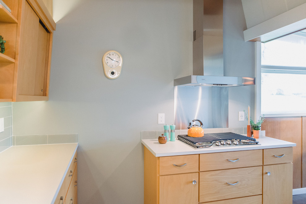 Small 1950s galley medium tone wood floor and gray floor enclosed kitchen photo in Grand Rapids with a drop-in sink, flat-panel cabinets, light wood cabinets, laminate countertops, gray backsplash, glass tile backsplash, stainless steel appliances, no island and beige countertops