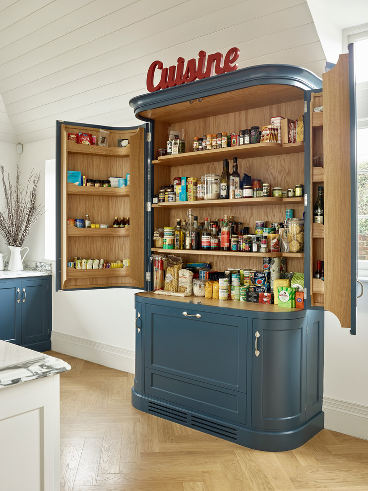 Example of a country light wood floor kitchen pantry design in Kent with recessed-panel cabinets and blue cabinets