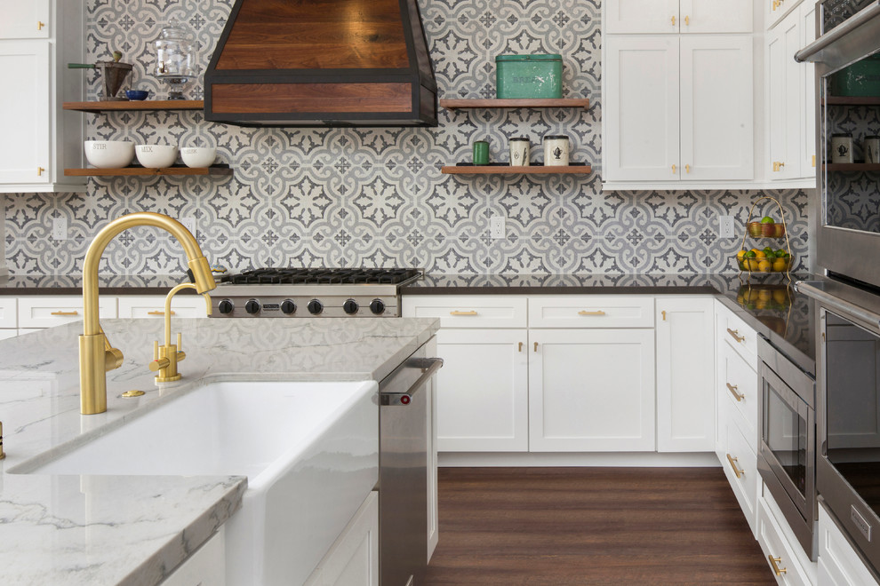 Inspiration for a mid-sized transitional l-shaped dark wood floor and brown floor eat-in kitchen remodel in Sacramento with a farmhouse sink, shaker cabinets, white cabinets, gray backsplash, cement tile backsplash, stainless steel appliances, an island and marble countertops
