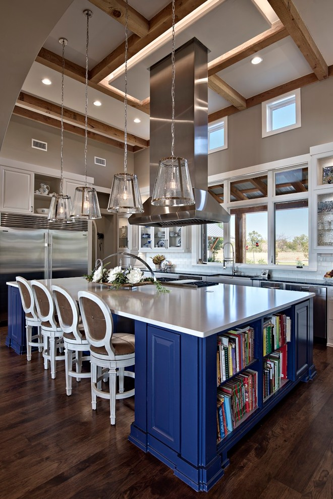 Inspiration for a large transitional galley dark wood floor open concept kitchen remodel in Austin with a farmhouse sink, raised-panel cabinets, blue cabinets, marble countertops, white backsplash, ceramic backsplash, stainless steel appliances and an island