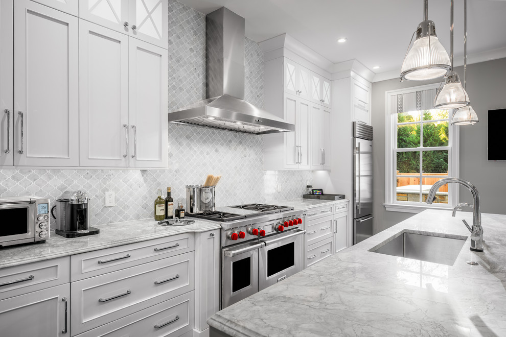 Example of a large classic galley medium tone wood floor kitchen design in Philadelphia with white cabinets, marble countertops, gray backsplash, stone tile backsplash, stainless steel appliances, an island, an undermount sink and recessed-panel cabinets