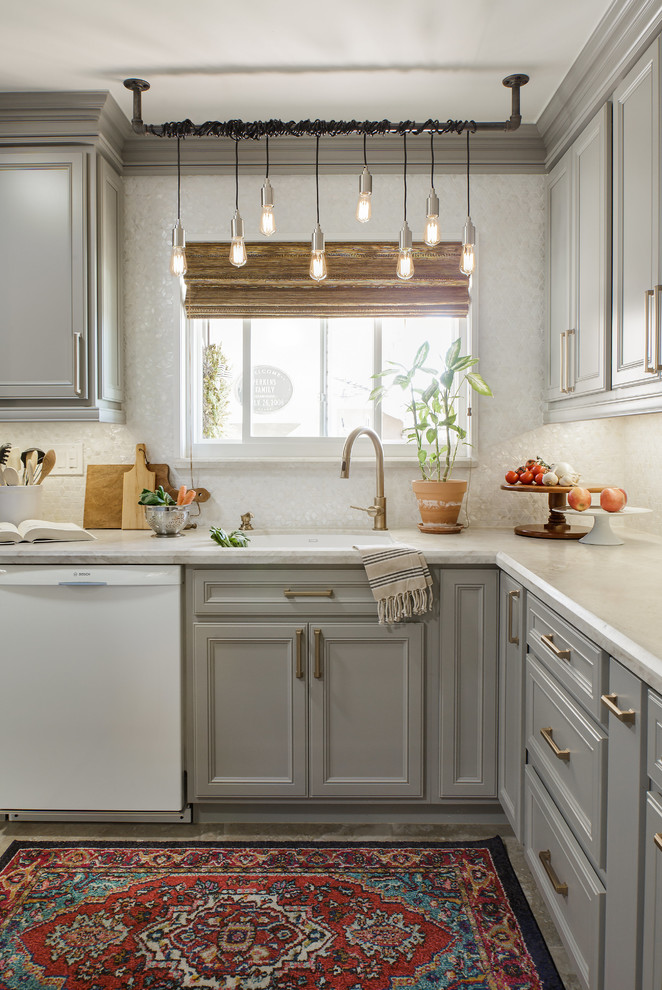 Small transitional l-shaped porcelain tile and beige floor kitchen photo in San Diego with recessed-panel cabinets, gray cabinets, quartzite countertops, white backsplash, white appliances, an island, mosaic tile backsplash, a single-bowl sink and white countertops