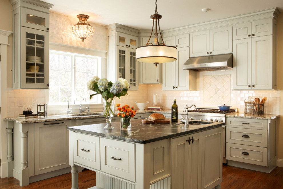 Open concept kitchen - mid-sized traditional u-shaped medium tone wood floor open concept kitchen idea in St Louis with soapstone countertops, recessed-panel cabinets, white backsplash, subway tile backsplash, stainless steel appliances, an undermount sink, gray cabinets and an island