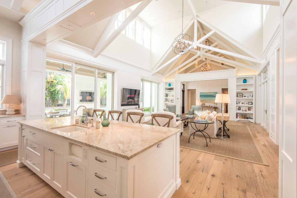 Inspiration for a large cottage l-shaped light wood floor open concept kitchen remodel in Tampa with a farmhouse sink, shaker cabinets, white cabinets, marble countertops, white backsplash, ceramic backsplash, paneled appliances and an island