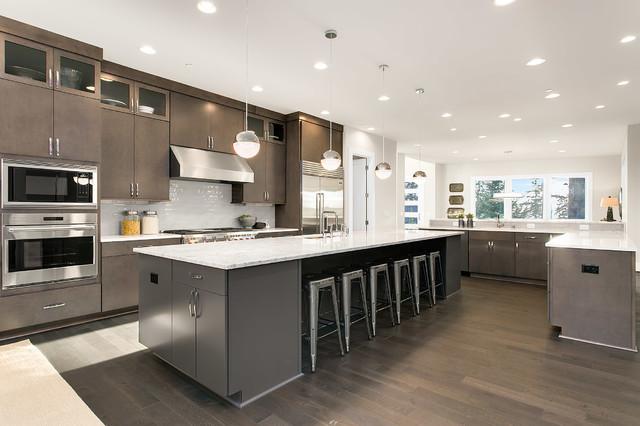 Kitchen - contemporary dark wood floor kitchen idea in Seattle with flat-panel cabinets, quartz countertops, stainless steel appliances, an undermount sink, dark wood cabinets and white backsplash