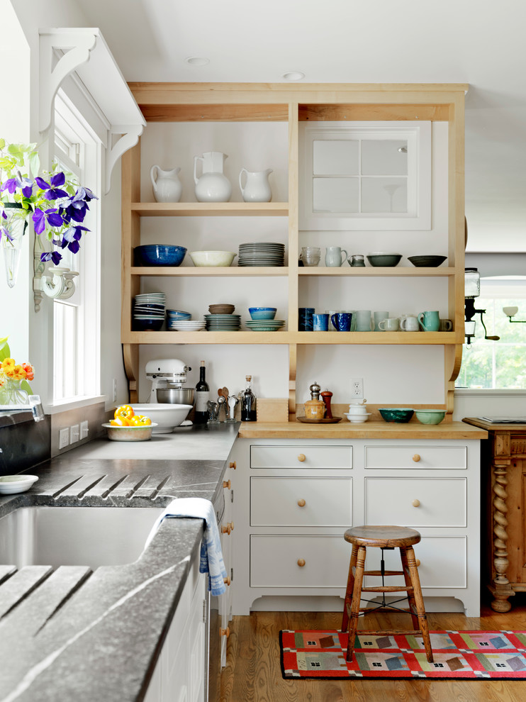 Example of a farmhouse kitchen design in Burlington with an undermount sink, open cabinets and wood countertops