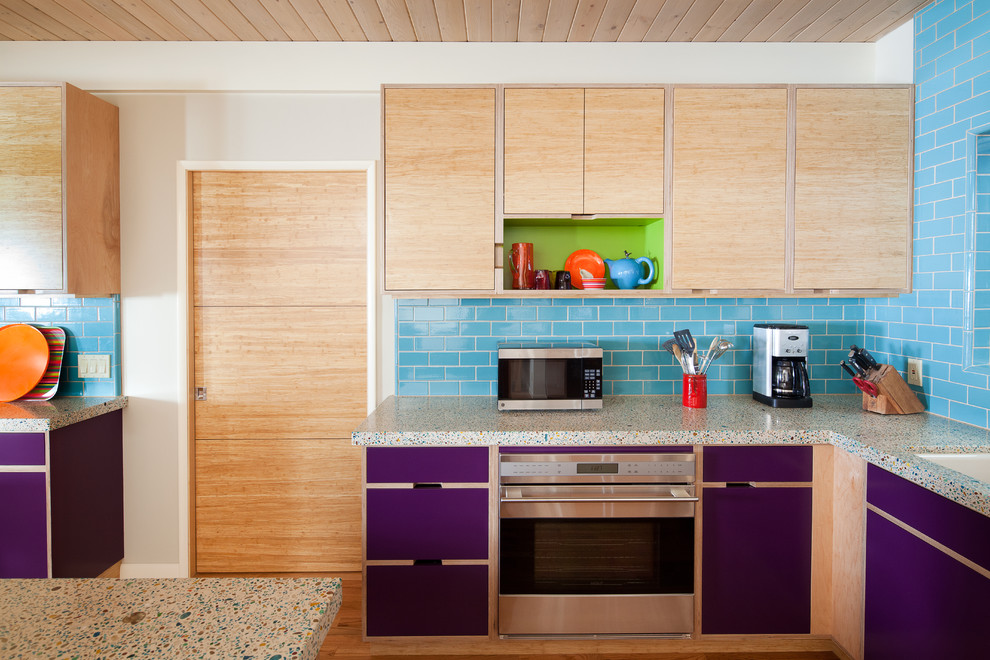 Eat-in kitchen - mid-sized eclectic u-shaped medium tone wood floor and brown floor eat-in kitchen idea in San Luis Obispo with stainless steel appliances, flat-panel cabinets, light wood cabinets, subway tile backsplash, an undermount sink, blue backsplash, a peninsula, recycled glass countertops and multicolored countertops