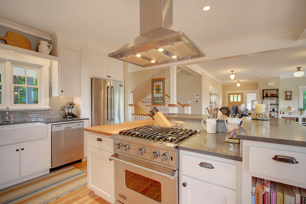 Example of a mid-sized arts and crafts l-shaped light wood floor eat-in kitchen design in Seattle with stainless steel appliances, a farmhouse sink, recessed-panel cabinets, white cabinets, gray backsplash, subway tile backsplash and an island