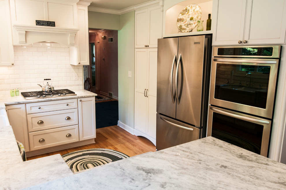 Inspiration for a small transitional u-shaped medium tone wood floor enclosed kitchen remodel in Milwaukee with a farmhouse sink, shaker cabinets, white cabinets, granite countertops, white backsplash, subway tile backsplash, stainless steel appliances and a peninsula