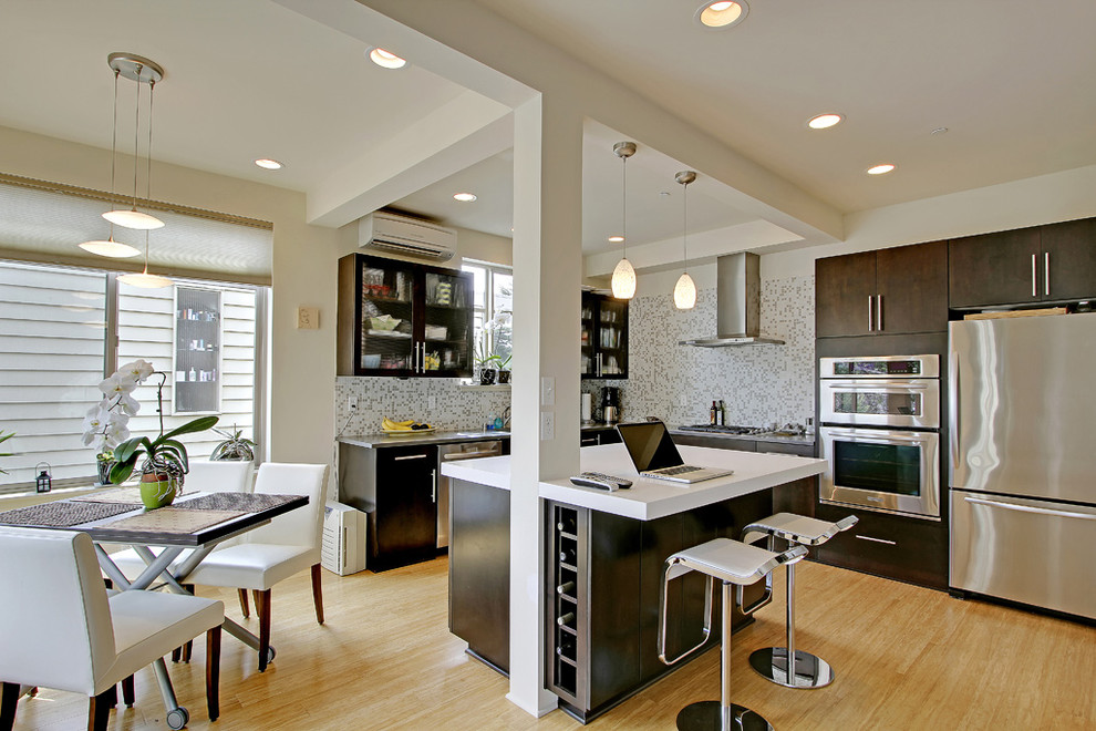 Example of a trendy kitchen design in Seattle with mosaic tile backsplash and stainless steel appliances