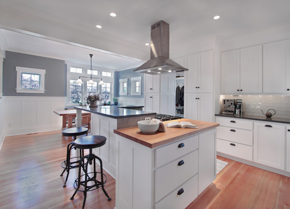 Eat-in kitchen - mid-sized craftsman l-shaped medium tone wood floor and brown floor eat-in kitchen idea in Seattle with wood countertops, shaker cabinets, white cabinets, white backsplash, glass tile backsplash, an undermount sink, stainless steel appliances, an island and gray countertops