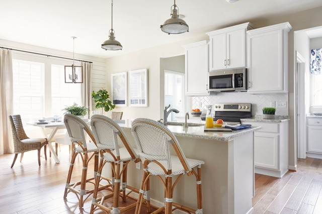 Example of a coastal light wood floor eat-in kitchen design in Other with an undermount sink, recessed-panel cabinets, white cabinets, white backsplash, stainless steel appliances, an island and gray countertops