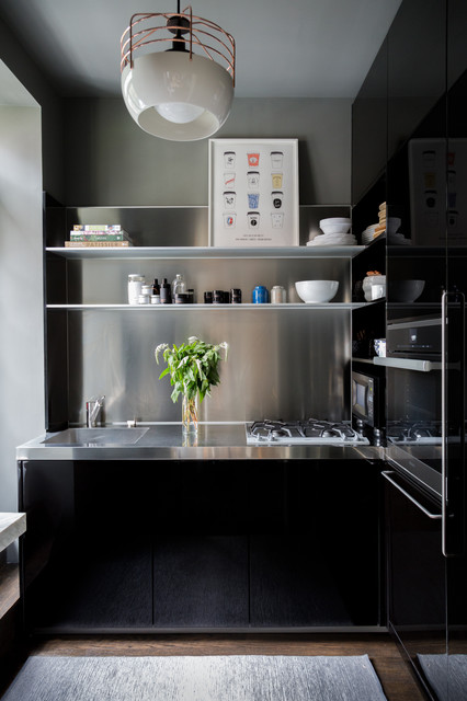 Small trendy dark wood floor kitchen photo in New York with an integrated sink, flat-panel cabinets, black cabinets, stainless steel countertops, metallic backsplash and no island