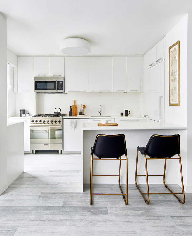 Inspiration for a mid-sized contemporary galley gray floor and vinyl floor eat-in kitchen remodel in New York with flat-panel cabinets, white cabinets, solid surface countertops, white backsplash, stainless steel appliances, an undermount sink, a peninsula, glass sheet backsplash and white countertops