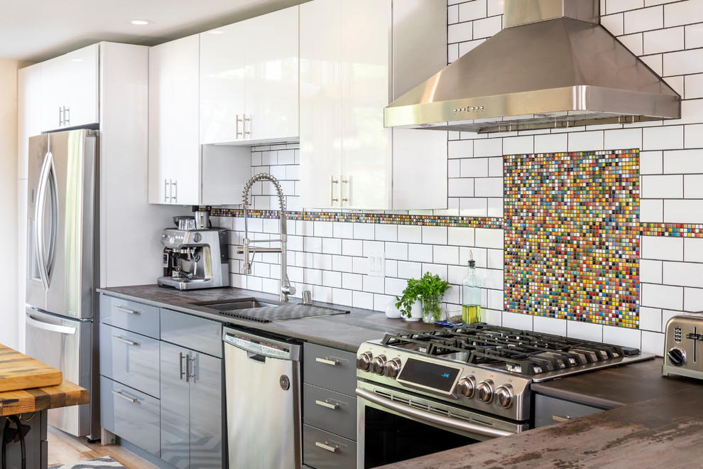 Inspiration for an industrial kitchen remodel in Seattle with an undermount sink, flat-panel cabinets, gray cabinets, multicolored backsplash, mosaic tile backsplash, stainless steel appliances and brown countertops