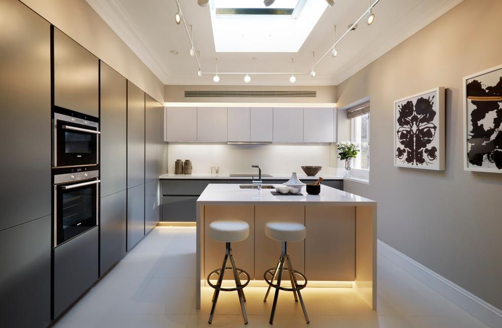 Modelo de cocinas en L gris y blanca, actual, con fregadero bajoencimera, armarios con paneles lisos, puertas de armario grises, salpicadero blanco, electrodomésticos de acero inoxidable y una isla