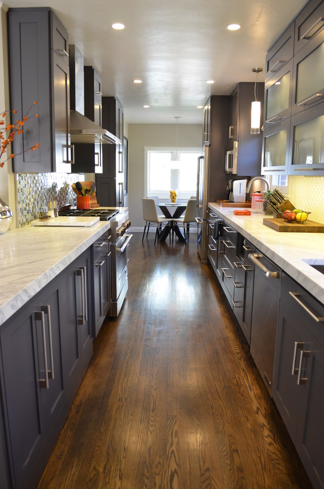 Example of a large trendy galley dark wood floor kitchen design in Sacramento with an undermount sink, shaker cabinets, gray cabinets, marble countertops, white backsplash, stainless steel appliances and no island