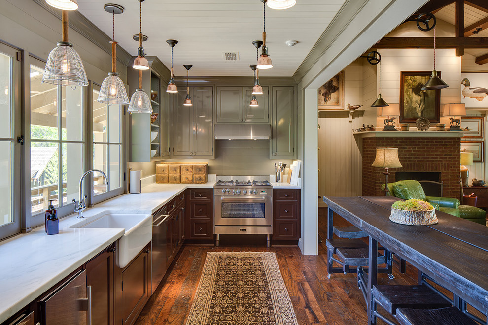 Example of a mid-sized farmhouse l-shaped dark wood floor and brown floor open concept kitchen design in Nashville with a farmhouse sink, recessed-panel cabinets, brown cabinets, stainless steel appliances and an island