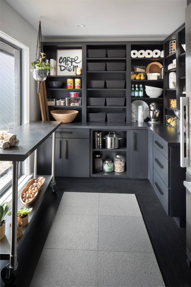 Example of a huge transitional l-shaped dark wood floor and black floor kitchen pantry design in Indianapolis with flat-panel cabinets, black cabinets, solid surface countertops, stainless steel appliances and an island