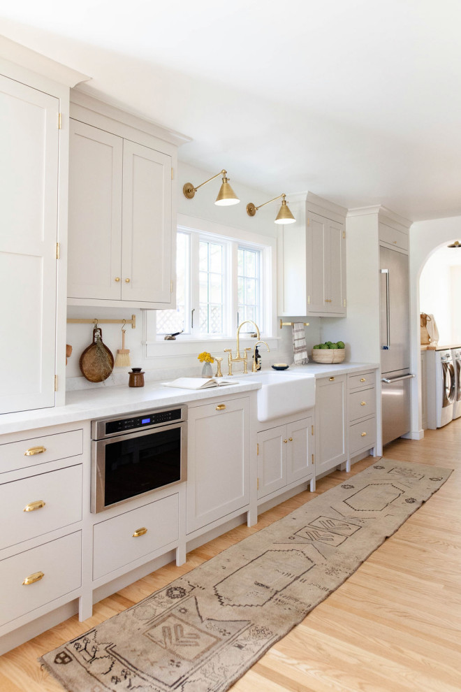 Transitional light wood floor and beige floor enclosed kitchen photo in Sacramento with a farmhouse sink, shaker cabinets, gray cabinets, stainless steel appliances and white countertops