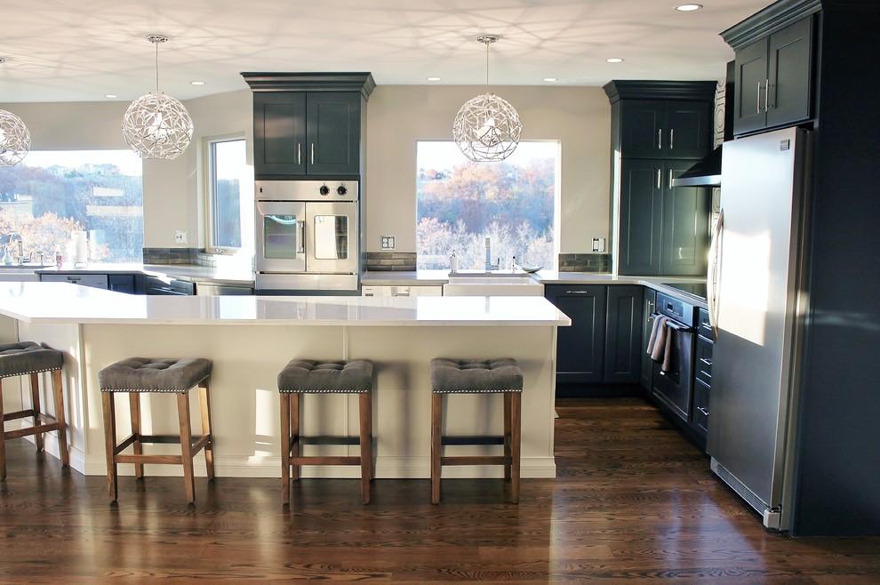 Large transitional u-shaped dark wood floor eat-in kitchen photo in Philadelphia with a farmhouse sink, shaker cabinets, blue cabinets, quartz countertops, gray backsplash, porcelain backsplash, stainless steel appliances and an island